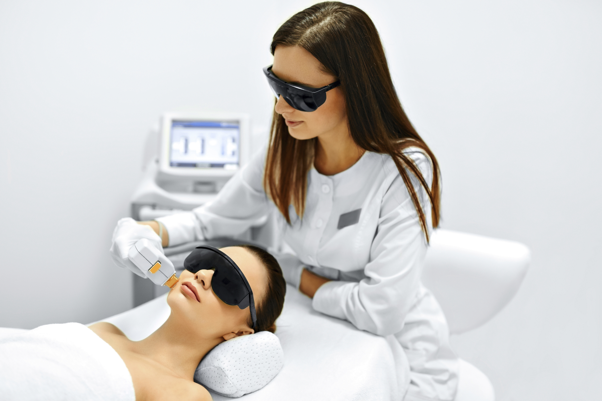 technician performing laser therapy to the face of a relaxed female patient, both wearing protective eyewear