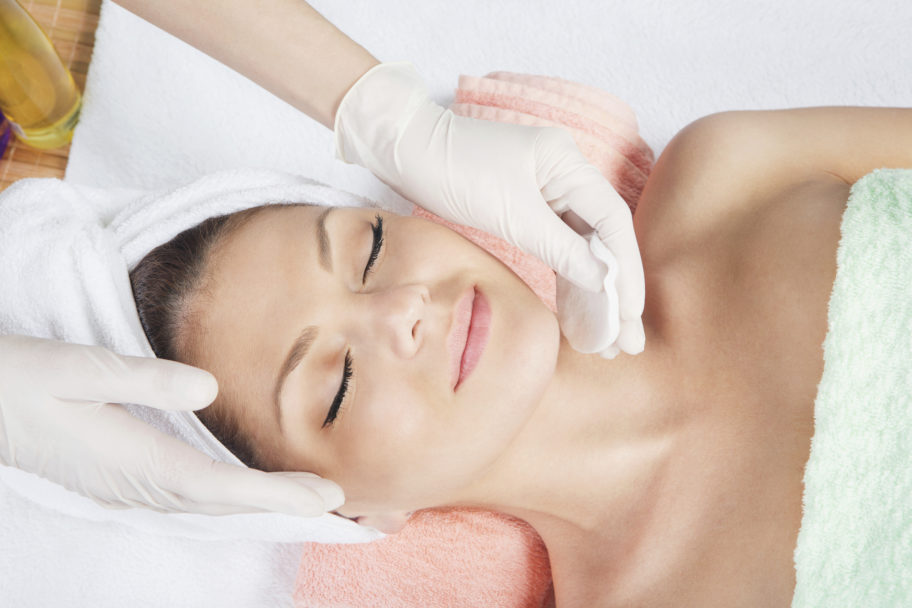 relaxed, beautiful woman receiving a facial treatment
