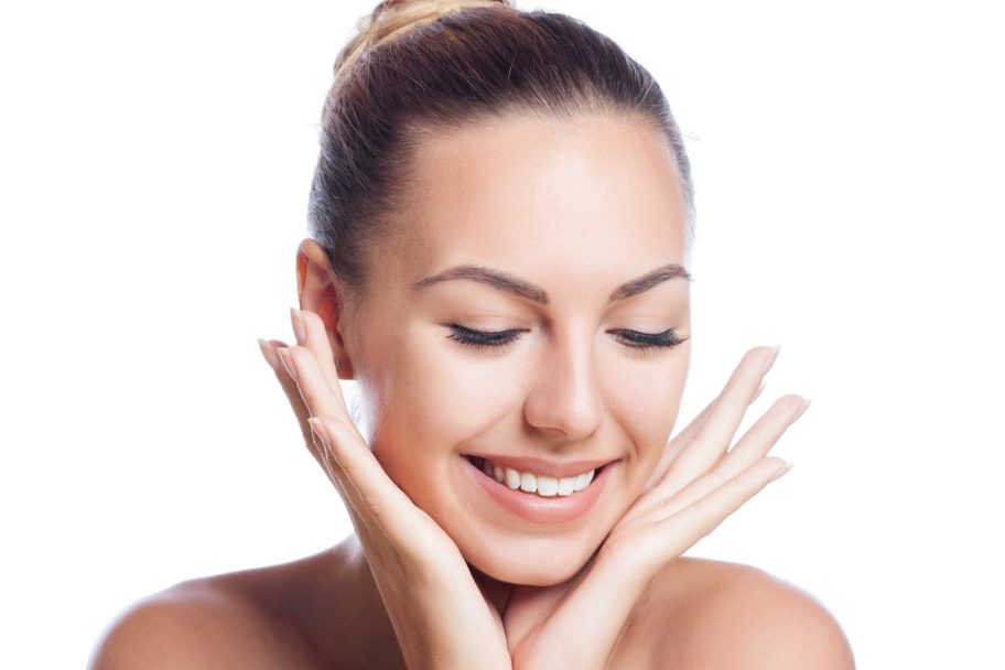 smiling, beautiful woman with tight facial skin, cupping her face in her hands