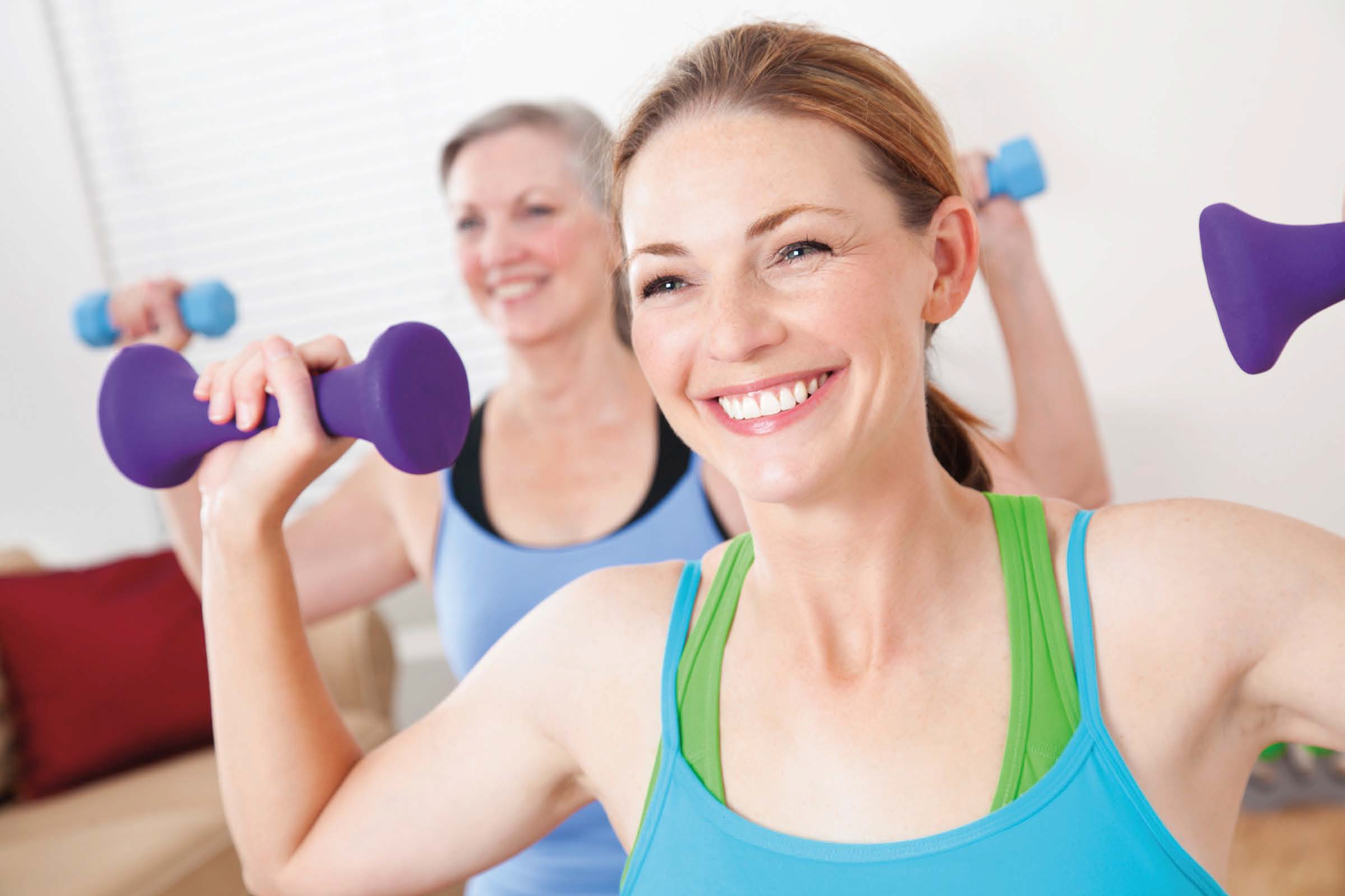 smiling middle-aged woman lifting hand weights in an exercise class
