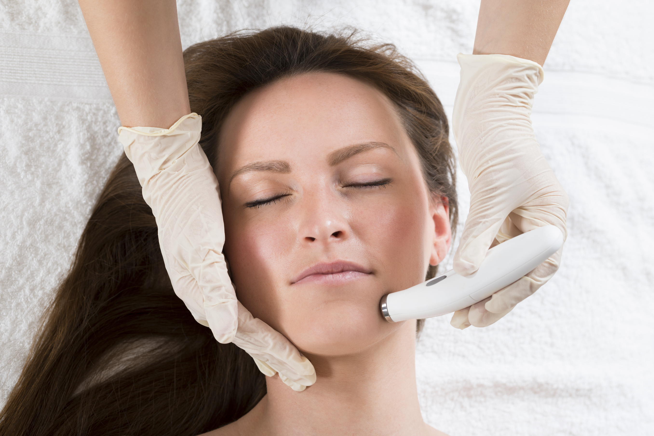 Doctor administering a microneedling treatment to a beautiful African American patient