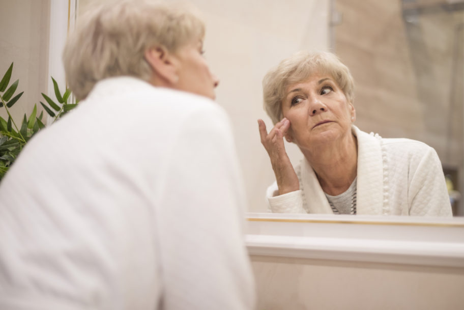 older woman examining facial skin in the mirror